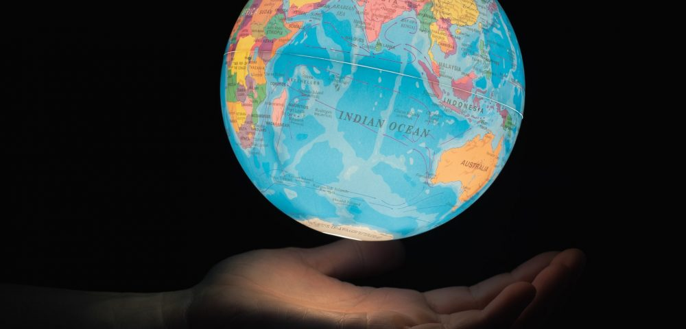 Desk globe in a mans hands