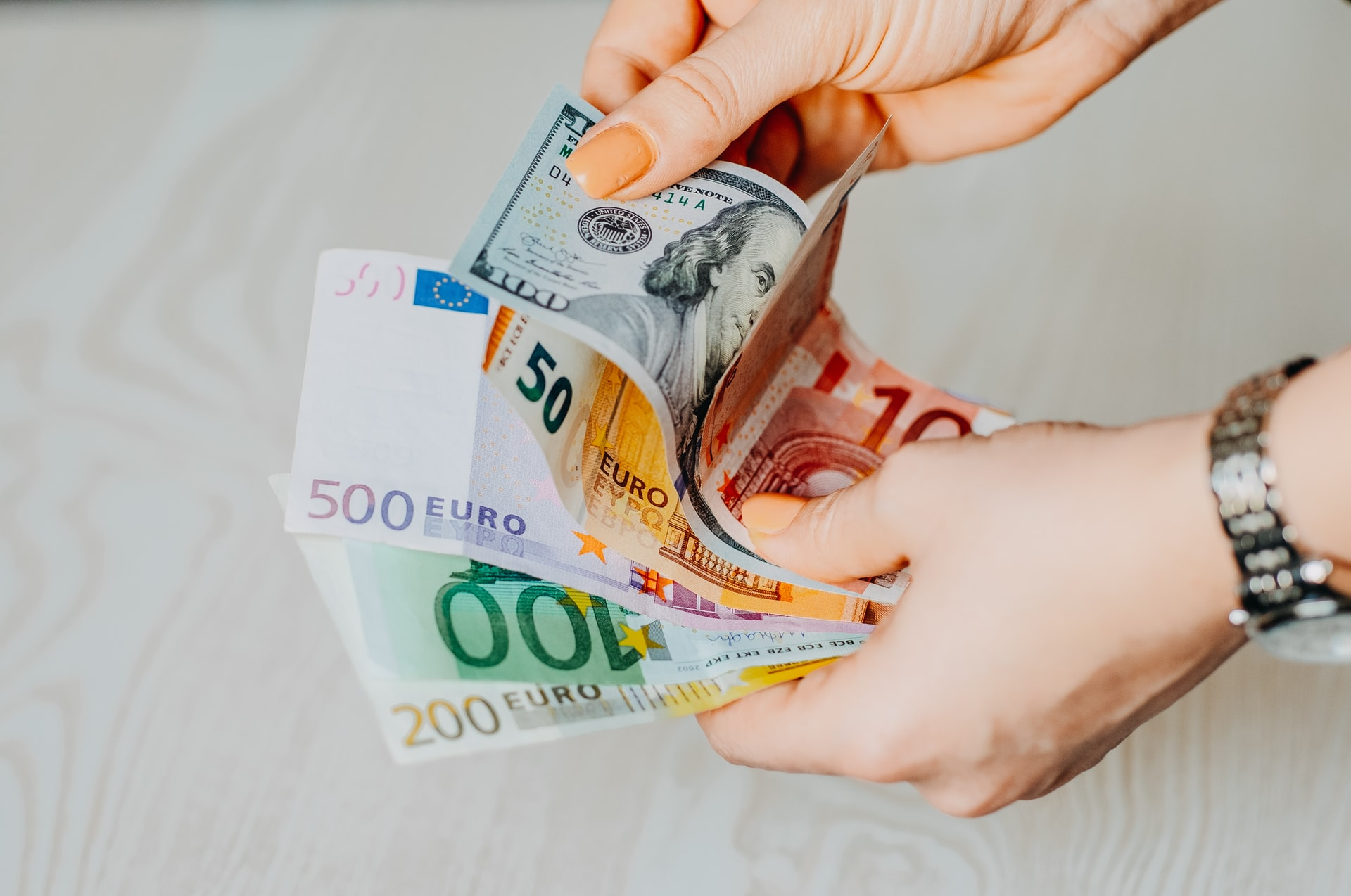 Person holding Euros and dollars